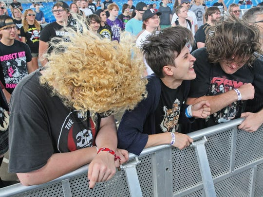 Fans at the front of the stage shake their heads and hair up and down as they listen to Valient Thorr perform.