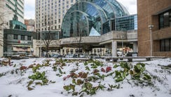 Snow blankets a garden outside of the PNC Center near