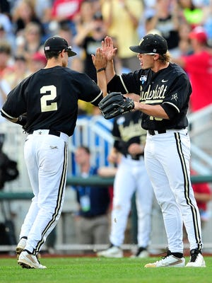 Vanderbilt pitcher Carson Fulmer, right, high fives with Tyler Campbell during the first inning against Virginia at the College World Series on Wednesday, June 25, 2014.