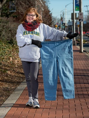 Diana Levering holds a pair of her old pants that she used to wear before she started to loose weight from working out.   Diana lost 70 pounds in the past year and a half.