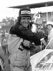 Darrell Waltrip hugs his trophy in victory lane after winning the Rebel 500 stock car race at Darlington Raceway in Darlington, South Carolina, in 1977.
