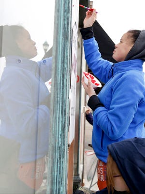 Elmira junior Kendra Davis, top, and Watkins Glen freshman Amber Updike paint messages combating tobacco use Friday on the windows of a Water Street building in Elmira.