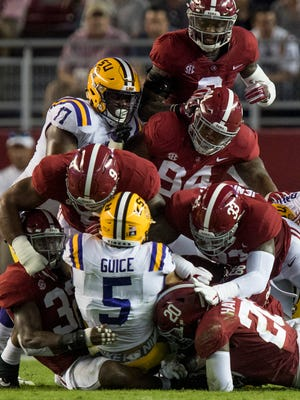 LSU runningback Derrius Guice (5) is stopped by Alabama linebacker Rashaan Evans (32), linebacker Shaun Dion Hamilton (20), defensive lineman Da'Shawn Hand (9) and linebacker Anfernee Jennings (33) in first half action at Bryant Denny Stadium in Tuscaloosa, Ala. on Saturday November 4, 2017.