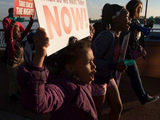 Ka'Mya Campbell, 8, center, chants along with her sisters and cousins during the Take Back the Night march at Dress Plaza in Downtown Evansville Thursday evening.