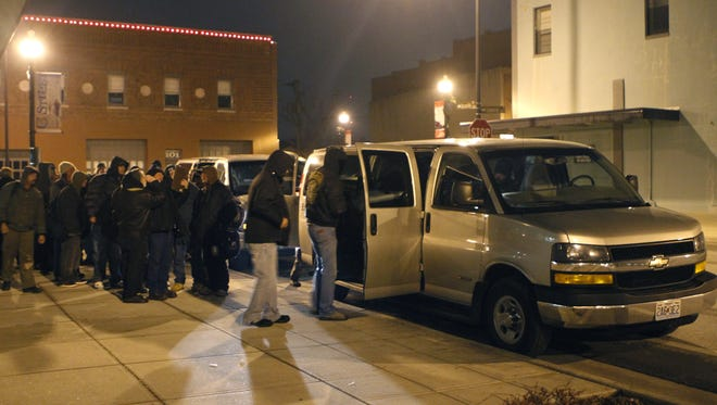 In this 2011 file photo, vans from East Sunshine Church of Christ pick up homeless men to bring to the church's emergency cold weather shelter.