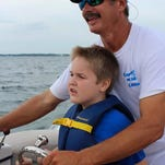 Steve Potate captains a boat for a young child during his Captains for Kids event last Saturday.