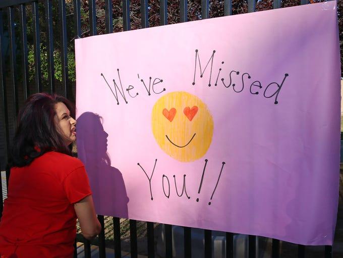 Mandy Ochoa, secretary to the principal, hangs signs