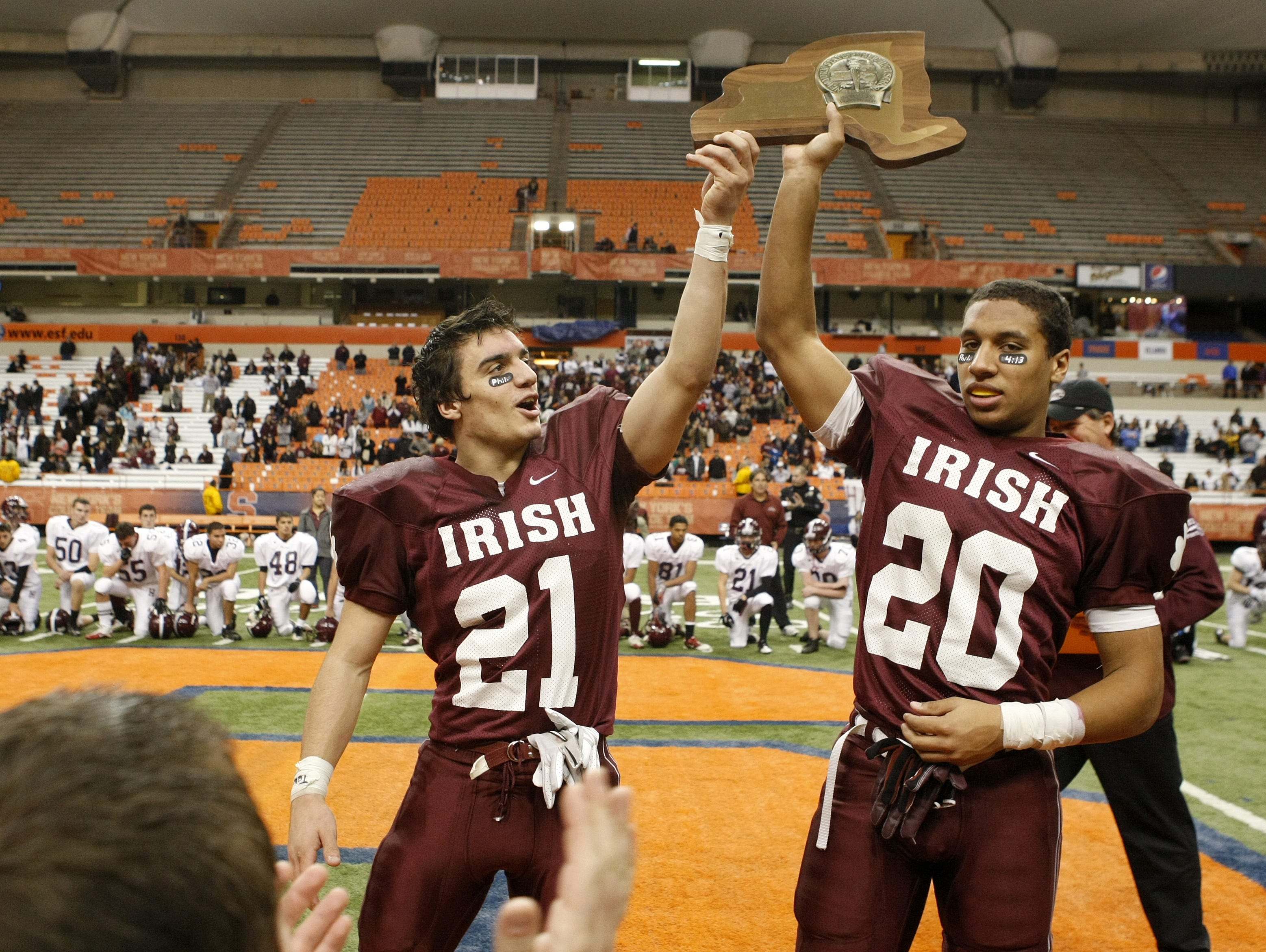 Aquinas senior captains Mike Messina (21), left, and Chris Bostick hoist the 2010 Class A championship trophy after the state final.
