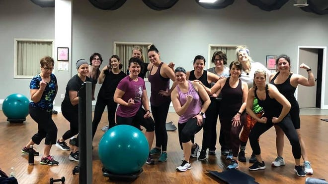A group of members pose at Girlfriends Fitness Club in February. The club will reopen following Gov. Gretchen Whitmer's announcement that gyms across Michigan will no longer be mandated shut.