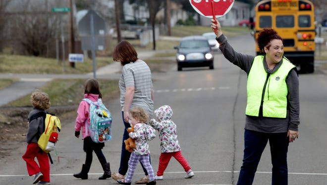 """Penni Robertson, 49 of Lake Orion, makes sure parents and their kids leave Carpenter Elementary School in Lake Orion safely and cross Flintridge Road on Wednesday, February 23, 2017.Robertson who has been the school crossing guard at the school for the past four years was named """"America's Favorite Crossing Guard"""" by Safe Kids Worldwide which is a global group that works for child school safety. She will be honored in a ceremony at the school on March 1st."""