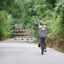 A cyclist rides toward a road closed sign on the Monon Trail near 146th Street, Carmel, on July 28, 2012. That part of the trail was closed while workers built a footbridge over 146th Street.