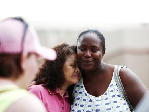 Eiko Gosden, left, is comforted by Angel Jones, who works with George at ElderHaus, during an organized search party for George Gosden at Christ Center Community Church Sunday, July 13, 2014.