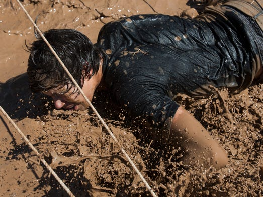 Participants run through mud-filled obstacle course at Mighty Mud Mania in Scottsdale on  June 8, 2013.