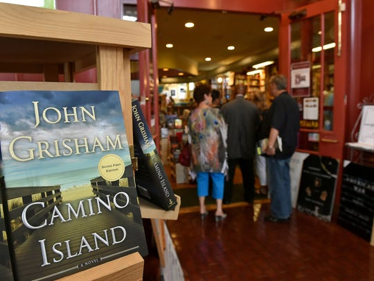 Fans of author John Grisham wait in line for him to sign his new book, Camino Island, Wednesday at Lemuria Books in Jackson.
