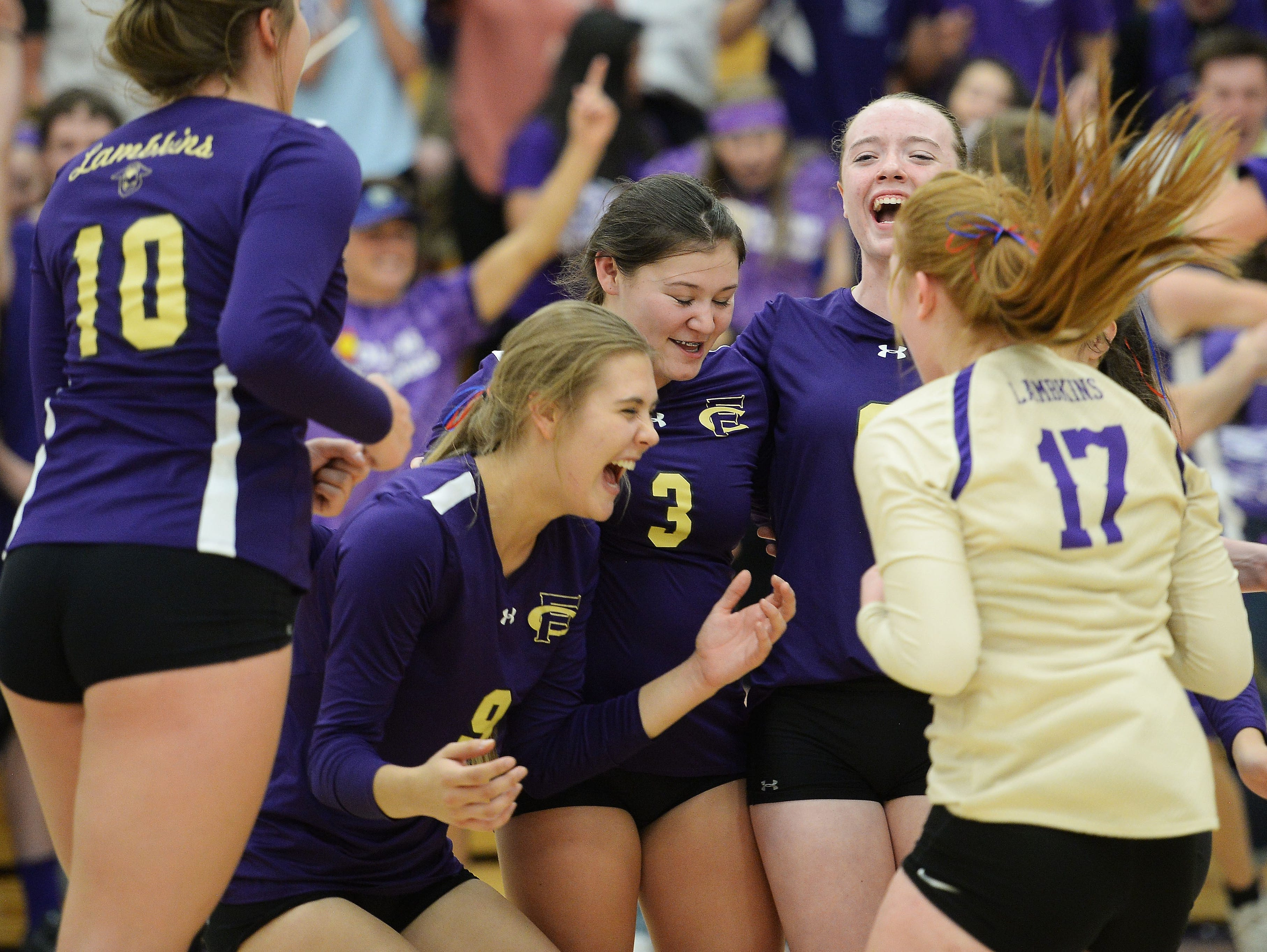 Fort Collins High School volleyball players celebrate a point during their sweep of rival Rocky Mountain on Tuesday night.