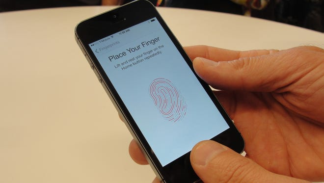 iPhone 5S handsets let people use their fingerprints to unlock the smartphones at an iPhone event at Apple's headquarters in Silicon Valley on September 10, 2013 in Cupertino, California.