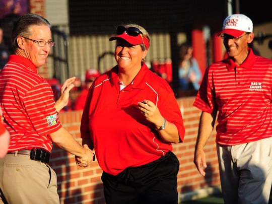 Former UL softball head coach Stefni Lotief receives a 2012 NCAA softball regional championship ring from athletic director Scott Farmer in 2013 as husband Michael looks on.