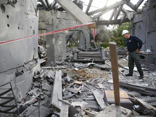A police officer inspects the damage to a house hit