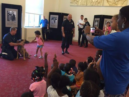 Three-year-old Trinati DiVigilio of Wilmington meets Wilmington Police Department K-9 Officer Greta at a super-hero themed summer reading program at Wilmington Library.