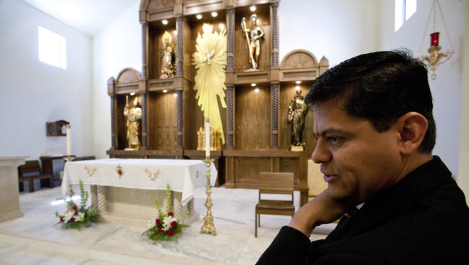 Father Gustavo Vidal describes the artwork inside St. George Catholic Church after its remodel in 2010.