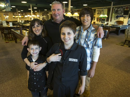 Matthew Webber, 14, Fishers, a pool trick-shot artist, is surrounded by family members: Nicholas Webber (brother), 7, Gizelle Webber (mother), Jesse Webber (father), and friend Parker Kjar, 14, at Jay Orner & Son Billiard Co. in Indianapolis.