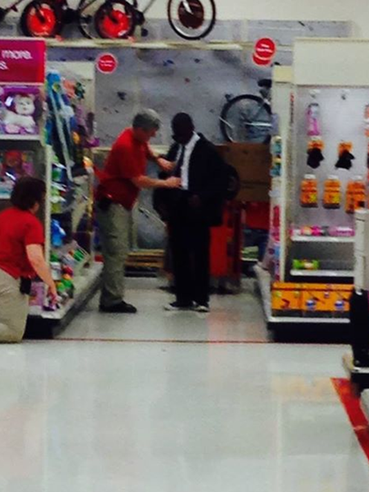 Target Worker Helps Young Man Tie A Tie For Interview