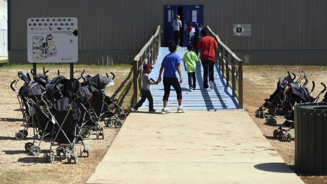 In this Aug. 9, 2018, file photo, provided by U.S. Immigration and Customs Enforcement, immigrants walk into a building at South Texas Family Residential Center in Dilley, Texas. Half a dozen families who were separated from their children at the U.S.-Mexico border are still detained in Texas months after reuniting with their children.