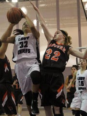 Katelyn Yuzos puts up a shot while being heavily guarded by two Capitan players.