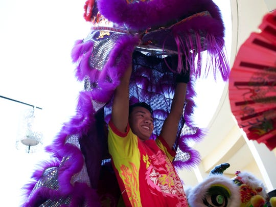 Nhan Phan, 18, performs a lion dance with other members of the Sunrise-based Lee Koon Hung Kung Fu Association as part of the 10th annual Asia Fest at the Mercato on Feb. 15, 2014.