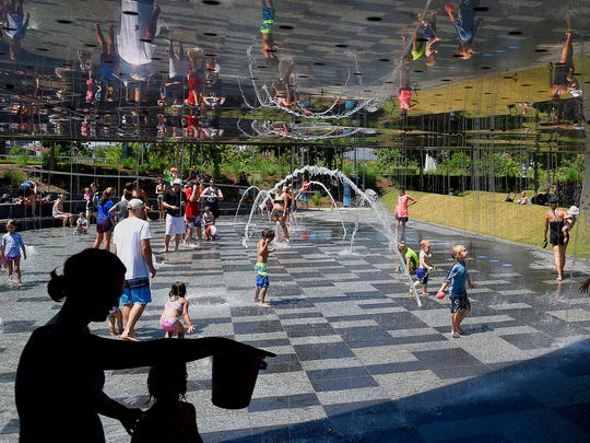 Children and their parents are reflected in a metal mirrored roof that serves as a crosswalk at the new Cumberland Park on June 16, 2016.