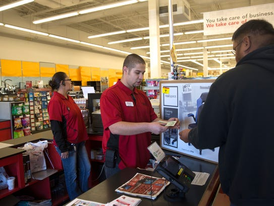 Office Depot OfficeMax logistics specialist Christo Martinez helps a customer at the register Friday in Farmington.