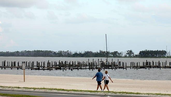 A couple enjoys a quiet walk along the Biloxi beach.