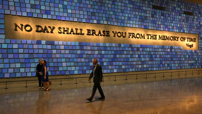 FILE - This May 15, 2014 file photo shows a quote from Virgil on a wall of the museum prior to the dedication ceremony at the National September 11 Memorial Museum in New York. More than 700,000 people have visited the 9/11 museum since it opened in May.