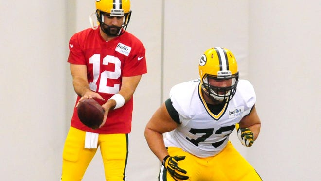 Green Bay Packers quarterback Aaron Rodgers works with center/guard JC Tretter during training camp practice in the Don Hutson Center, Monday, August 18, 2014.