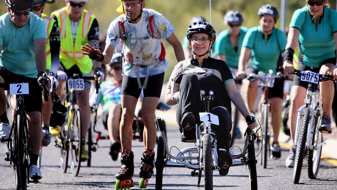 Former U.S. Rep. Gabrielle Giffords, front, rides in the El Tour de Tucson charity bike race on Saturday, Nov. 21, 2015, in Tucson, Ariz. Giffords was wounded in the 2011 shooting at a political event outside a Tucson grocery store where six people were killed.