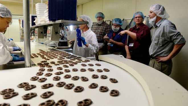 A group of visiting trade journalists watch cooled chocolate-covered pretzels get packaged at Wolfgang Candy Company's North York plant in 2014.
