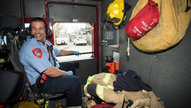 Port Huron firefighter Peter Lafata laughs at a joke told by one of the other firefighters while he rides in the back seat of a firetruck Thursday, April 5. Lafata is one of several firefighters hired by the department as the result of a voter-approved tax increase.