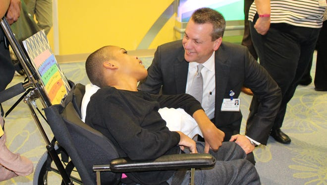 Children's Specialized Hospital President & CEO Warren Moore greets a pediatric patient.