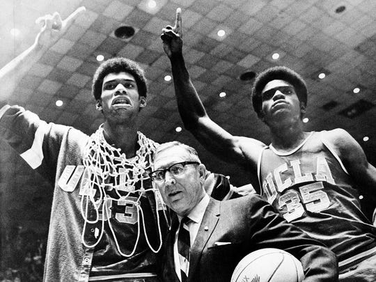 UCLA coach John Wooden is flanked by Sidney Wicks, right, and Lew Alcindor, draped with basket ropes, after the UCLA team beat Purdue 92-72 to win the NCAA basketball title in 1969 for the third consecutive year.