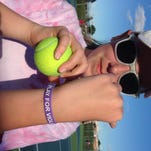 """Megan Hoffeditz shows off a purple bracelet that says """"Play For Violet,"""" which James Buchanan's girls tennis team will wear this season in honor of Violet Clark, who died in April."""