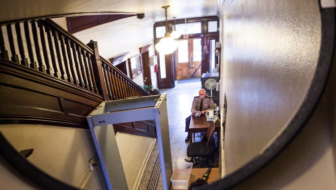 "Augusta County Sheriff's officer J.M. Wieger is reflected in a mirror that helps him see both the exit and entrance at Augusta County Circuit Court on Tuesday. ""I call it shotgun alley,"" said Wieger, describing the narrow hallway."
