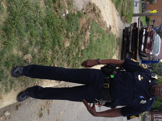 Sgt. Charles White stands in front of the wrecked Nissan Maxima that ran a stop sign and hit three pedestrians in Northside Sunday. You can see the skid marks on the left.