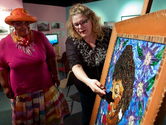 Artist Anita Prentice (right), of Fort Pierce, talks with Linda Henderson, chairwoman of ZoraFest, after unveiling her seventh mosaic of Zora Neale Hurston in 2011.