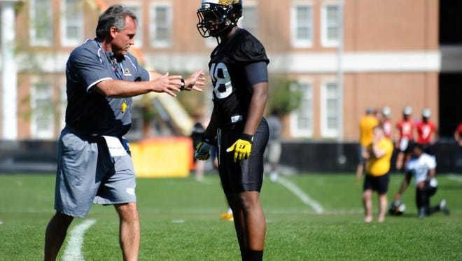 Southern Miss coach Jay Hopson demonstrates movements with Isaiah Spencer during the first day of spring practice on Tuesday.