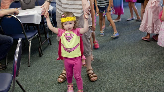 "Lorelei Lewis, 2, walks while holding hands with her mother, Gwyn Lewis, of North Street, during a Barbie-themed party to celebrate the new book ""Princess Power"" Tuesday at the St. Clair County Library."