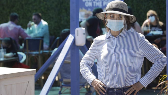 A hostess waits to sit customers on a restaurant at the pier Sunday in Santa Monica amid the coronavirus pandemic. A heat wave has brought crowds to California's beaches as the state grappled with a spike in coronavirus infections and hospitalizations and Monday closed several sectors.