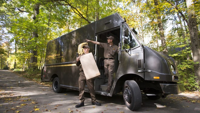 Andrew Sevier (left), trains with supervisor Mike Benson, while delivering packages for UPS, in Carmel, Friday, Oct. 28, 2016. Sevier will spend two weeks training in the classroom and on the road before being given his own truck.