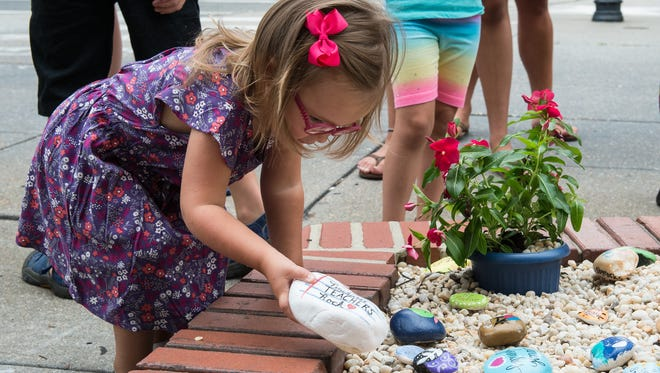 A young girl places a Kindness rock at Salisbury's newly opened Kindness Rocks garden at the corner of West Main Street and North Division Street on Monday, Aug. 14, 2017.