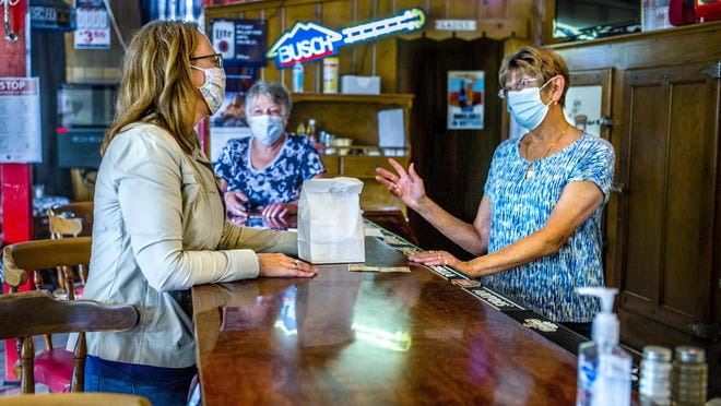 Castle's Patio Inn owner Barb Castle, right, and her sister, Kathy Crowe, center, talk with Cathy Setterland at the Peoria neighborhood bar/ restaurant Tuesday, July 14, 2020. Setterland stopped by to purchase a container of Castle's signature cheese spread.