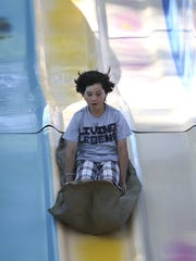 Marco Larios, 11, takes a trip down the giant slide